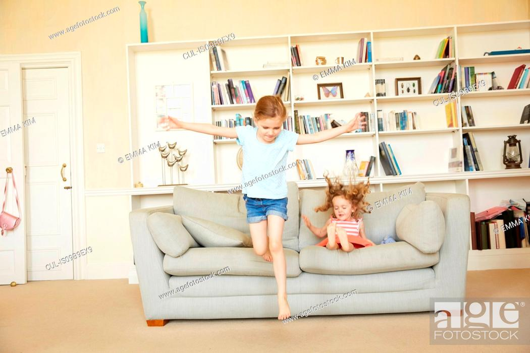 Stock Photo: Two young sisters jumping from and bouncing on sofa.