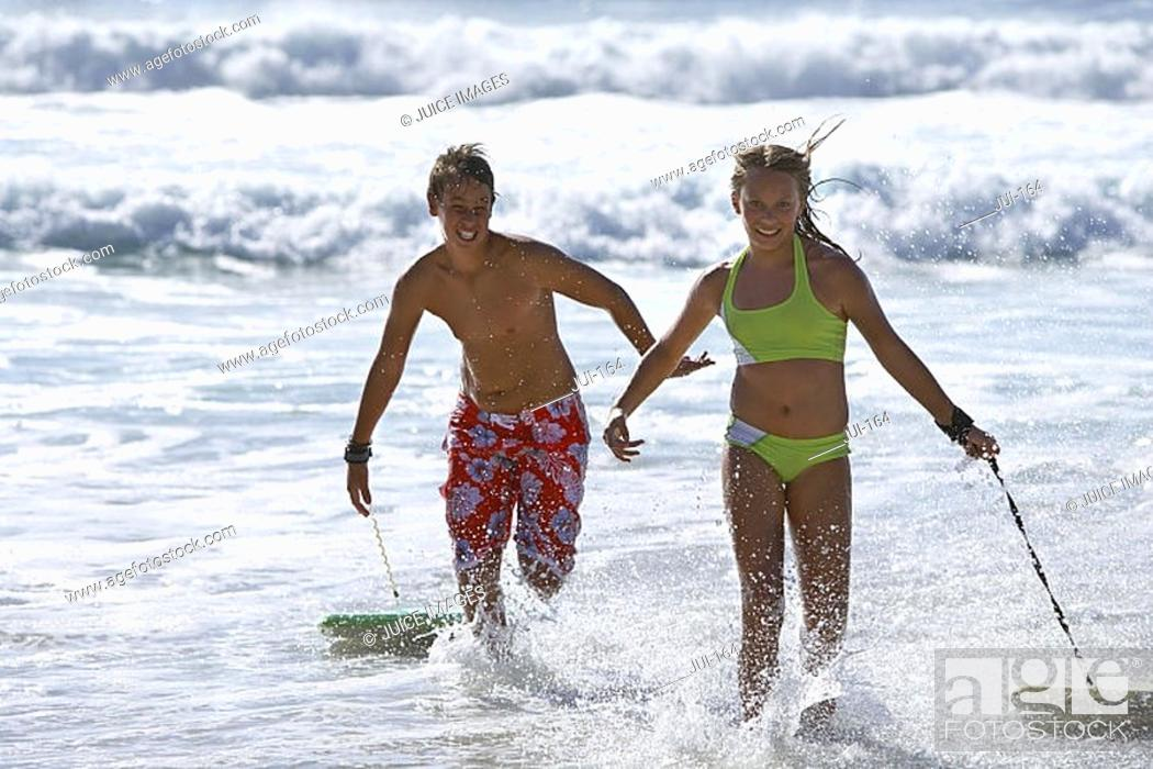 Stock Photo: Teenage boy and girl 13-15 exiting surf, pulling bodyboards over water, side by side, smiling.