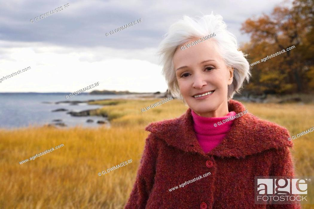 Stock Photo: Portrait of a senior woman smiling on the beach.