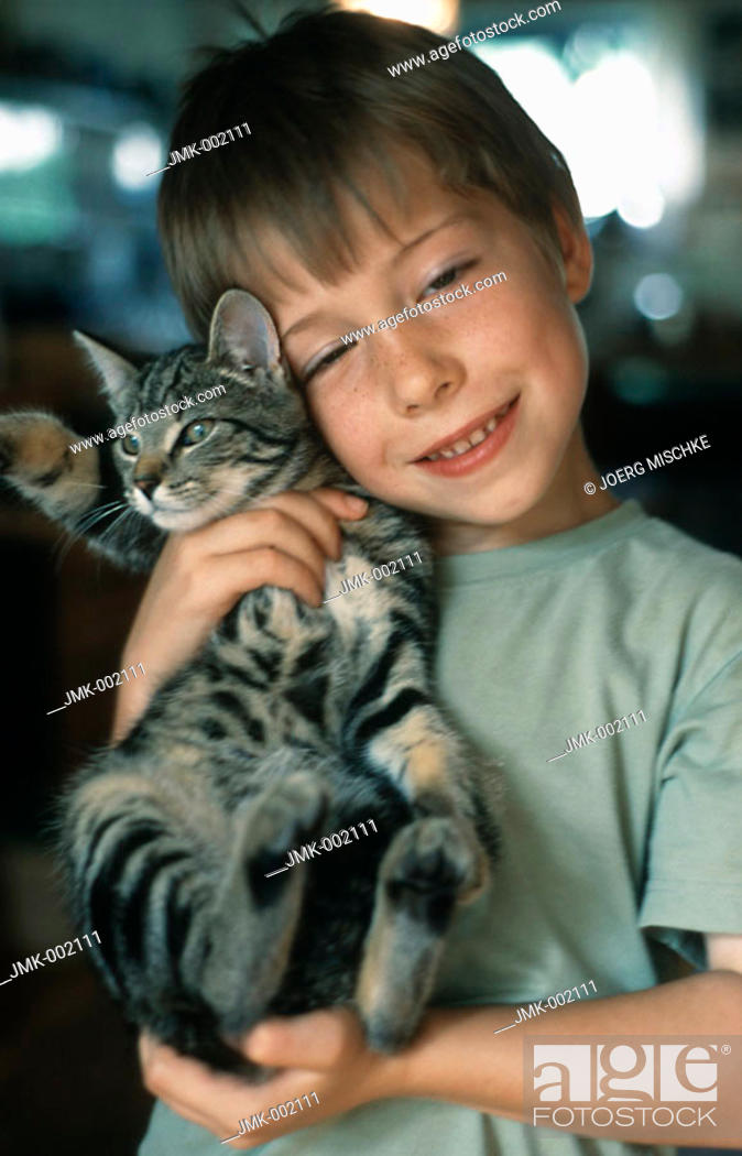 Stock Photo: A little boy, 5-10 years old, holding a cat.