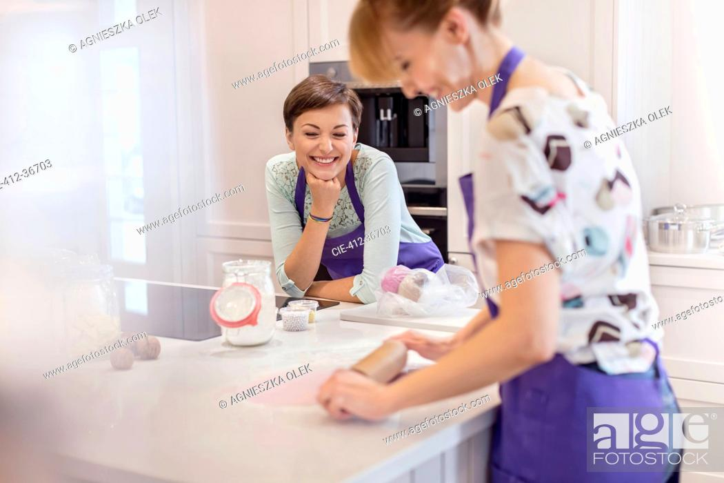 Stock Photo: Female caterers baking, using rolling pin in kitchen.