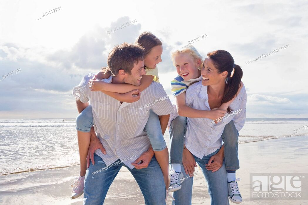 Imagen: Parents Giving Children Piggybacks On Beach Vacation.