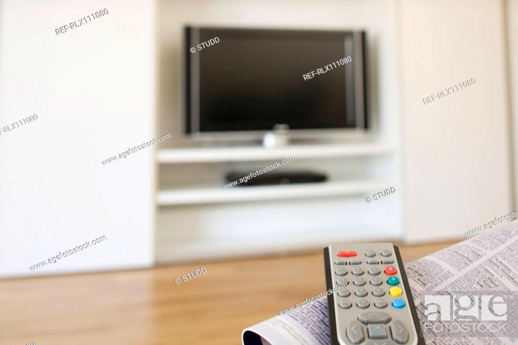 Stock Photo: Close up of TV remote control and magazine.