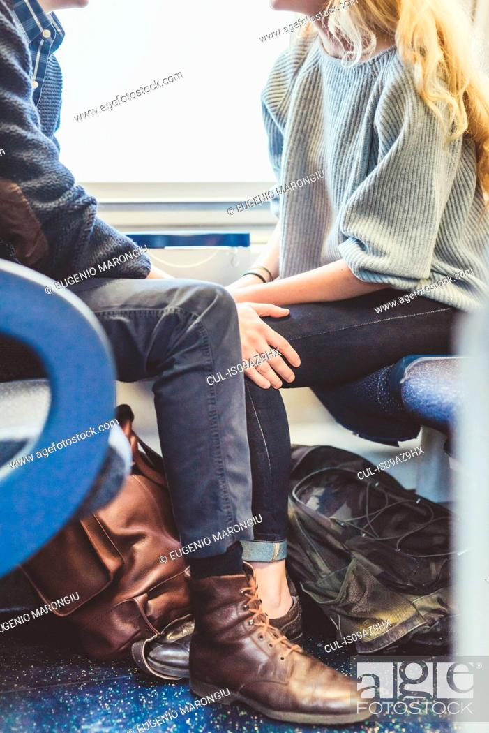 Stock Photo: Neck down view of romantic young couple travelling in train carriage, Italy.