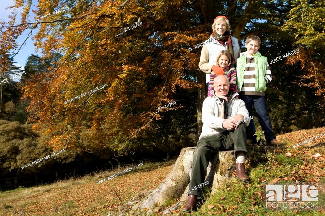 Stock Photo: Portrait of grandparents and grandkids in grass with autumn leaves.