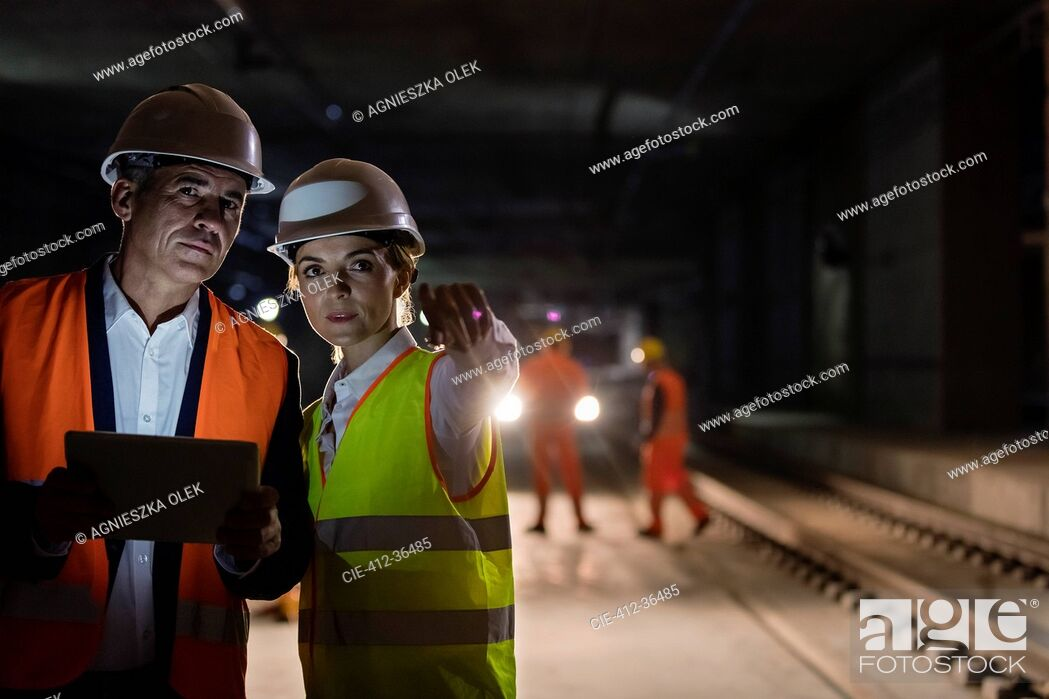 Stock Photo: Foreman and engineer with digital tablet talking on dark tracks at underground construction site.