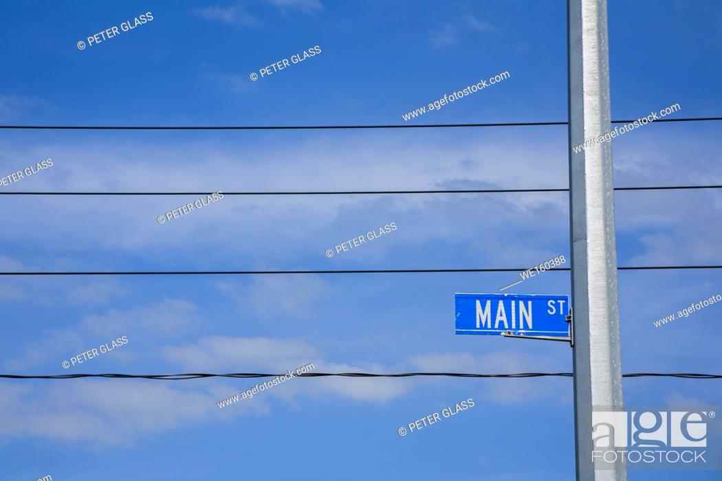 """Stock Photo: """"""""""""""""""""Main Street"""""""" sign with cloudy sky and telephone wires behind it."""