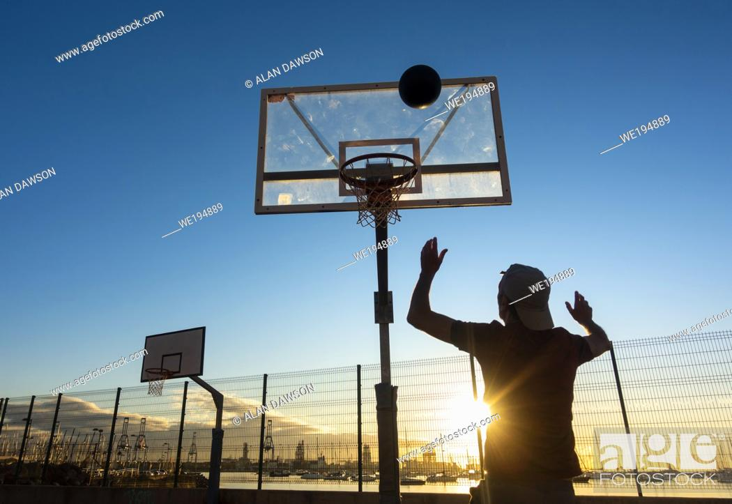 Stock Photo: Mature man playing Basketball on outdoor court at sunrise in Las Palmas, Gran Canaria, Canary Islands, Spain. Model released.