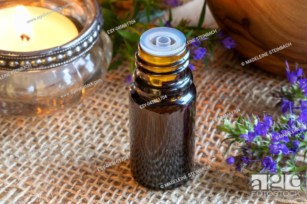 Stock Photo: A bottle of essential oil with fresh blooming hyssop twigs and a candle.