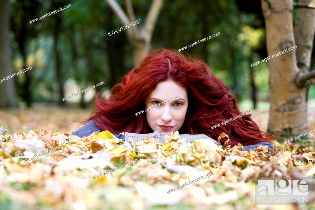 Stock Photo: A young woman lying amongst autumn leaves.