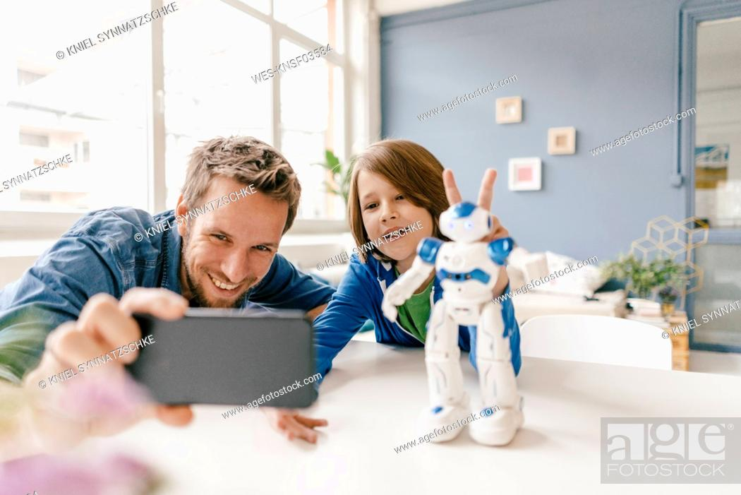 Stock Photo: Happy father and son taking a selfie with robot on table at home.
