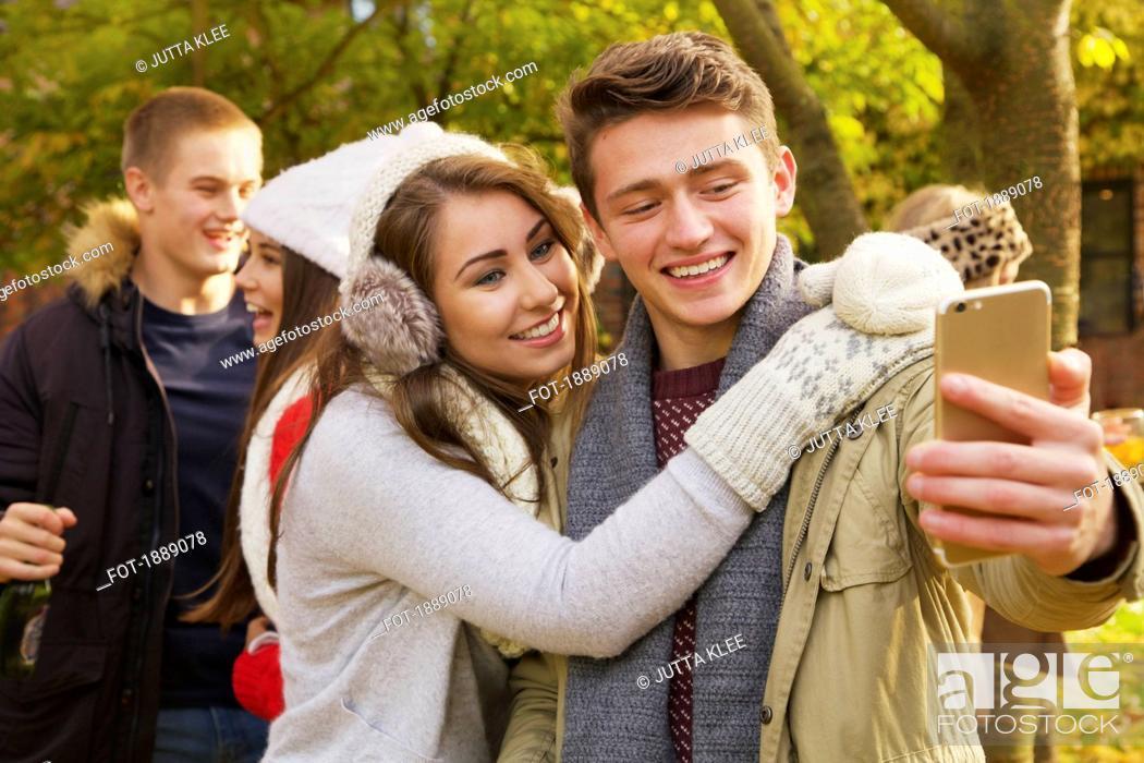 Stock Photo: Happy teenage couple taking selfie in autumn park.