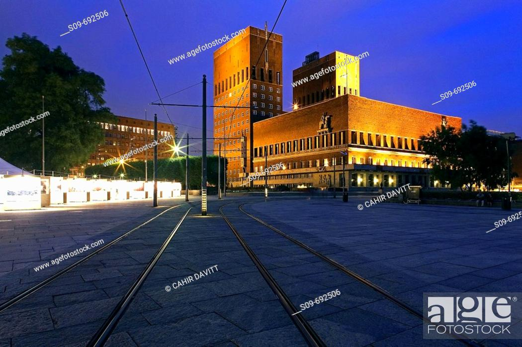 Stock Photo: Oslo Town Hall, seen from Aker Brygge with tram lines in the foreground, Oslo, Norway.
