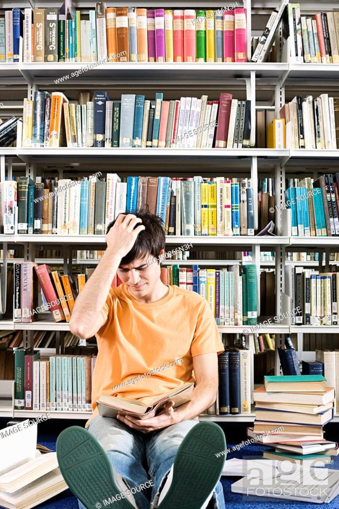 Stock Photo: Confused student in library.
