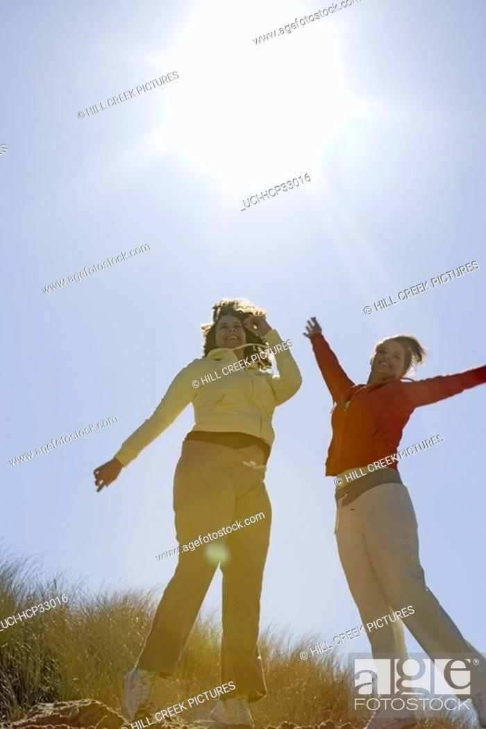 Stock Photo: Women jumping for joy at beach.