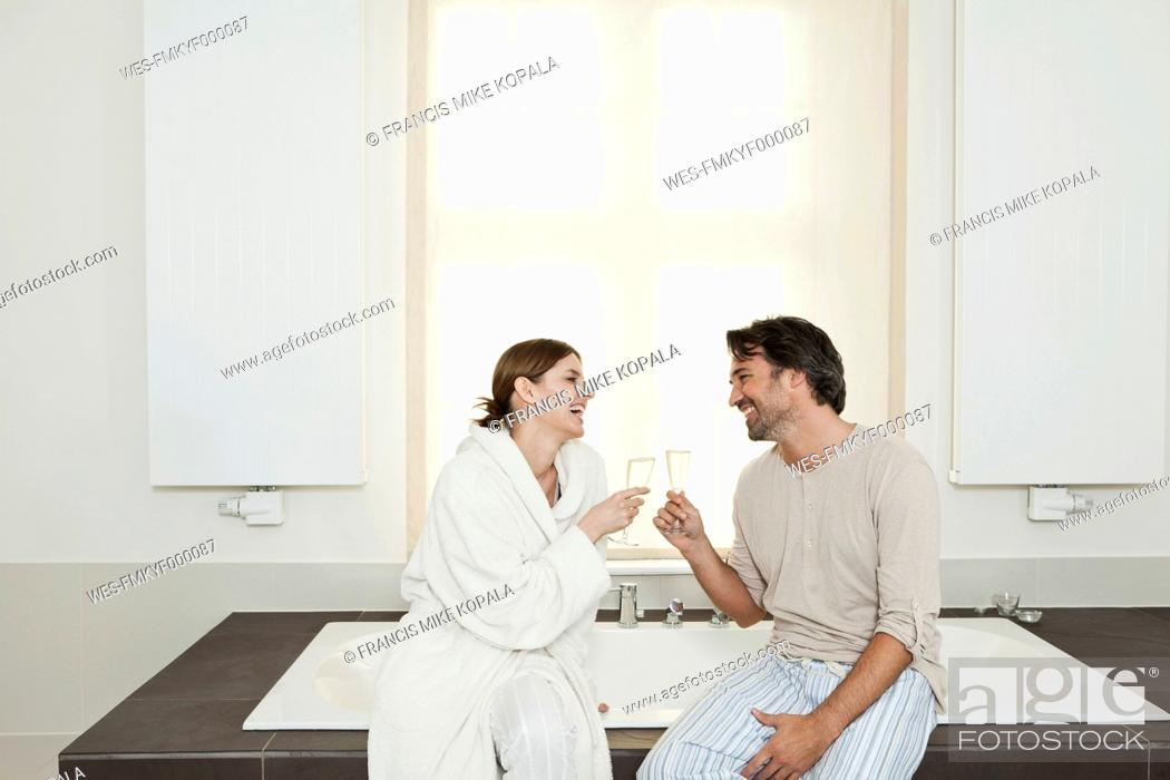 Stock Photo: Germany, Berlin, Mature couple sitting on bathtub with sparkling wine.