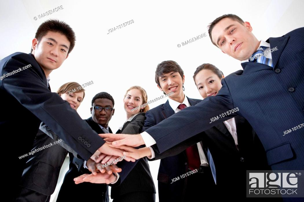 Stock Photo: Business People putting hands in a stack together and looking at the camera.