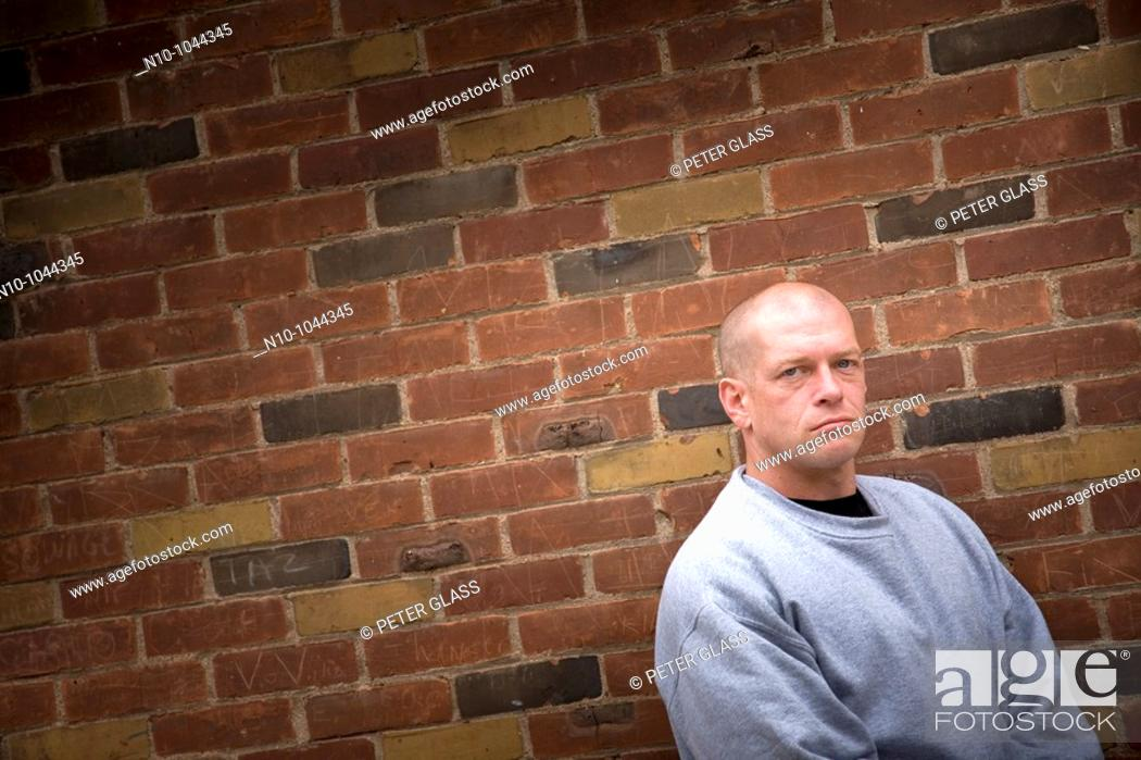 Stock Photo: Young bald man in front of a brick wall.