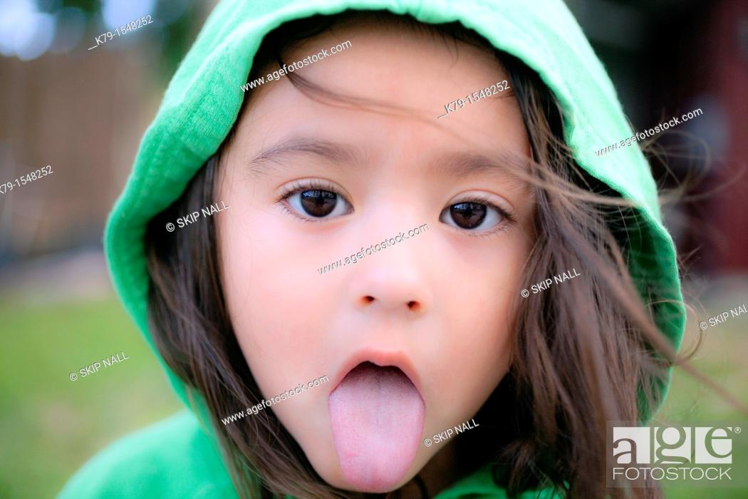Stock Photo: A little girl with her tongue sticking out looking sick.