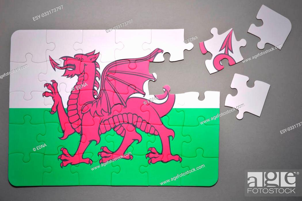 Stock Photo: broken puzzle with the national flag of wales on a gray background.