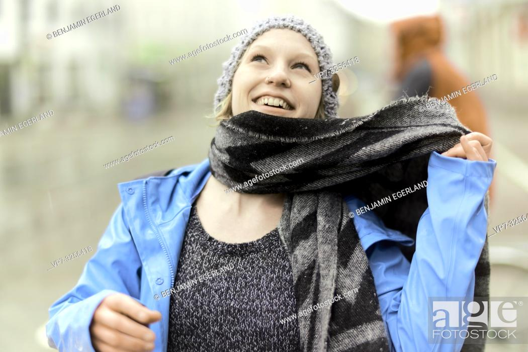 Stock Photo: happy optimistic woman with scarf outdoors in bad weather, in Munich, Germany.