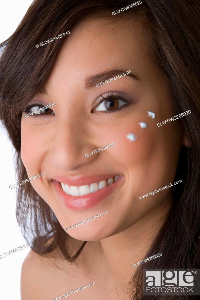 Stock Photo: Portrait of a young woman with cream on her cheek.