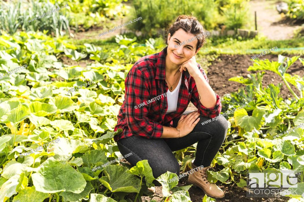 Stock Photo: Young woman with hand on chin kneeling amidst vegetables growing in garden.
