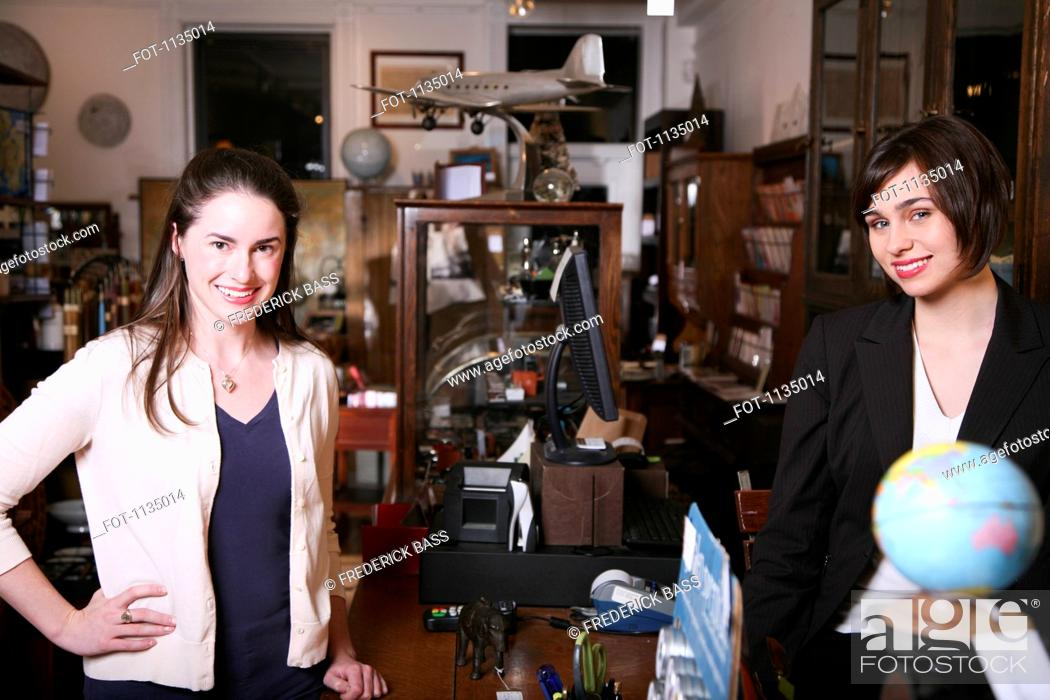 Stock Photo: Two women standing on opposites sides of a counter in an antiques shop.