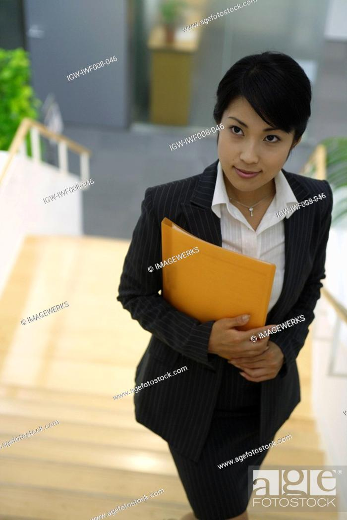 Stock Photo: A woman holding a file stands on the staircase.