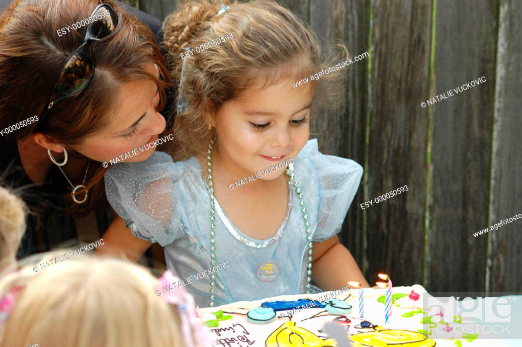 Stock Photo: Birthday girl with mother ready to blow out her candles.