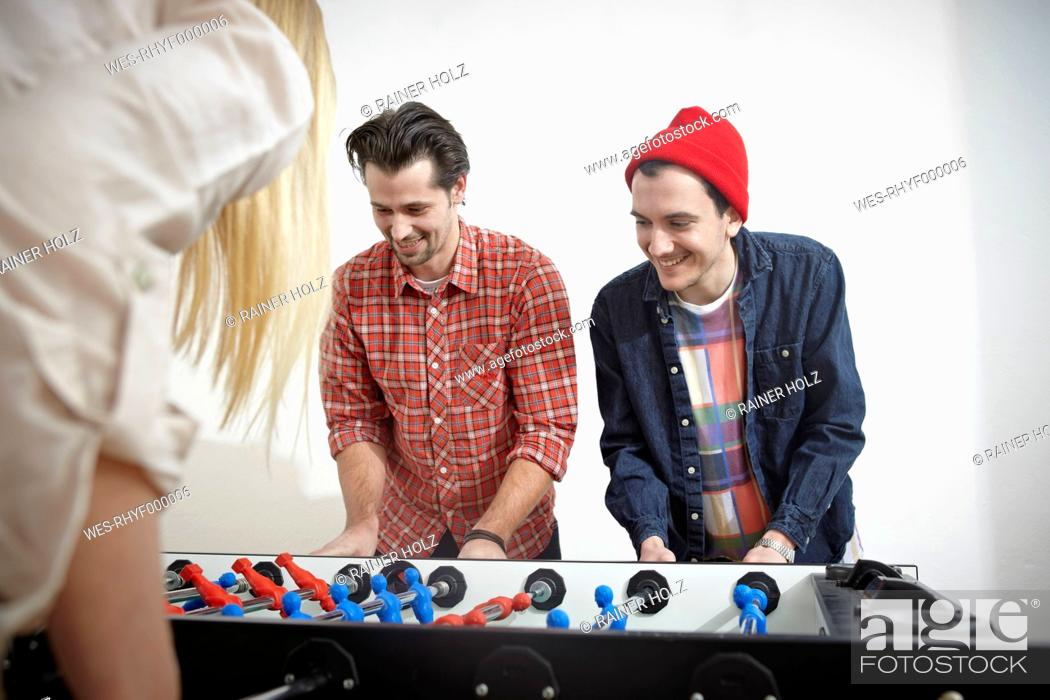 Stock Photo: Germany, Cologne, Men and woman playing table soccer, smiling.
