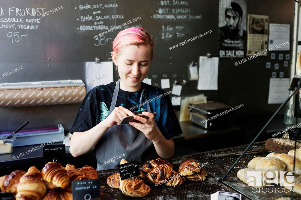 Stock Photo: Smiling owner photographing breads in coffee shop.