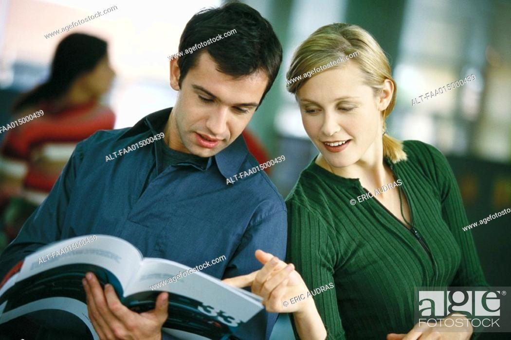 Stock Photo: Man holding brochure, woman looking over his shoulder, pointing to page.