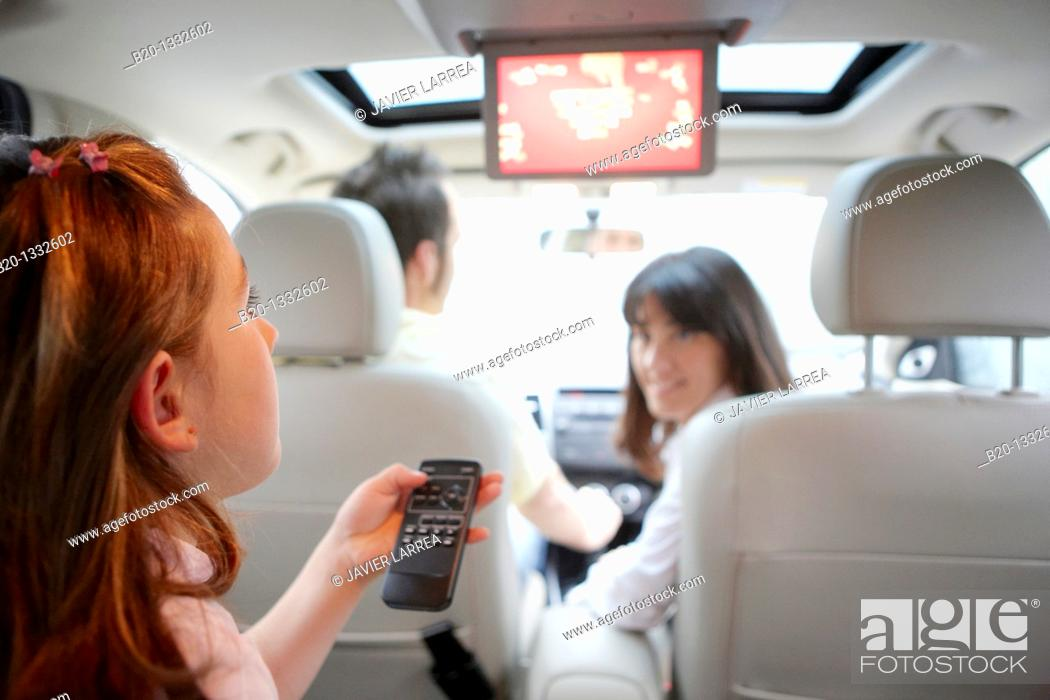 Stock Photo: Family travelling, girl watching DVD in car.