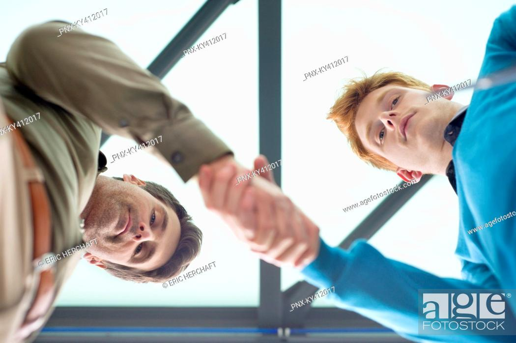 Stock Photo: Businessmen shaking hands in an office.