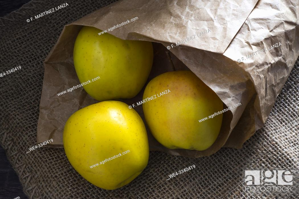 Stock Photo: Yellow apples wrapped in paper.