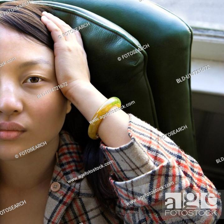 Stock Photo: Woman sitting in green chair with hands on her head.