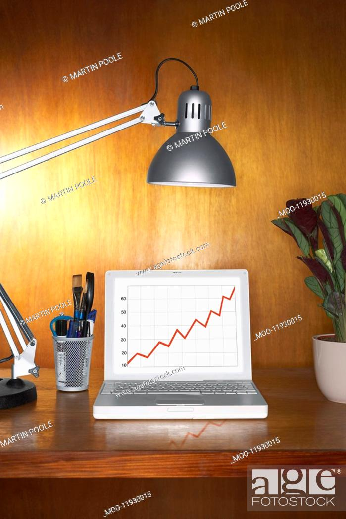 Stock Photo: Laptop showing graph and other items on desk.