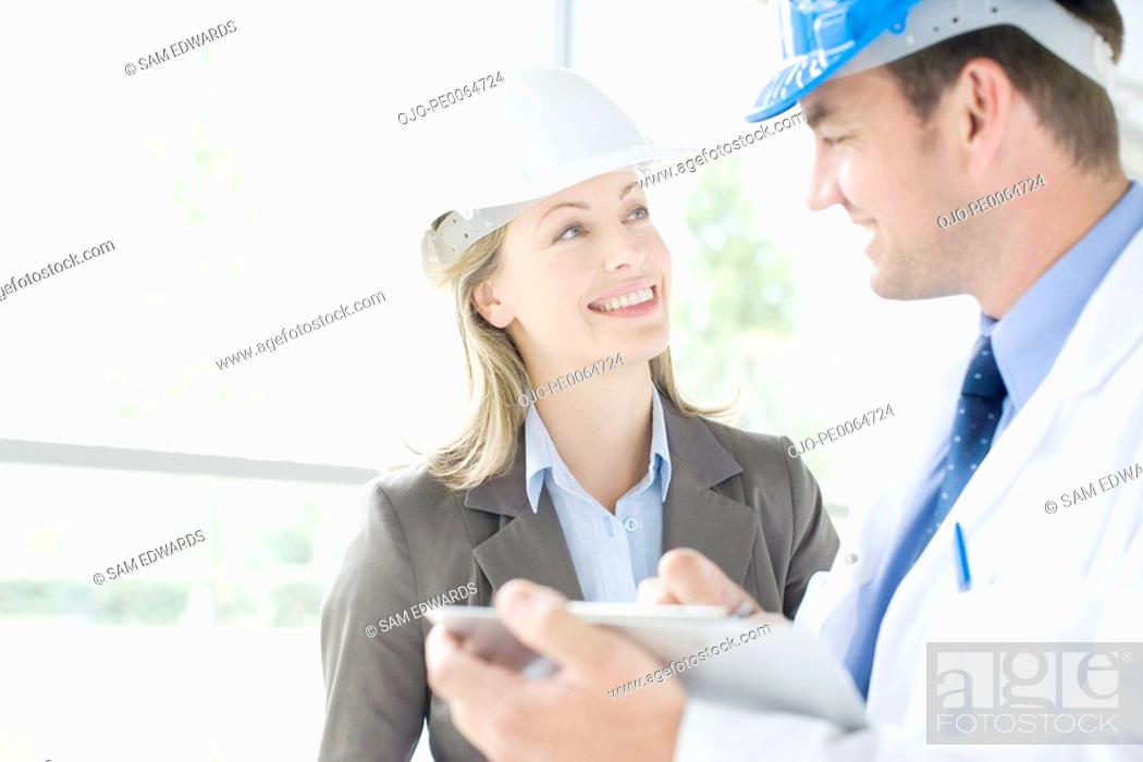 Stock Photo: Businesspeople working together in hard-hats.