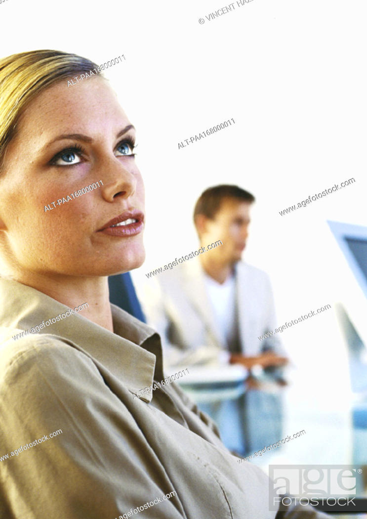 Stock Photo: Woman looking up, man sitting in background.