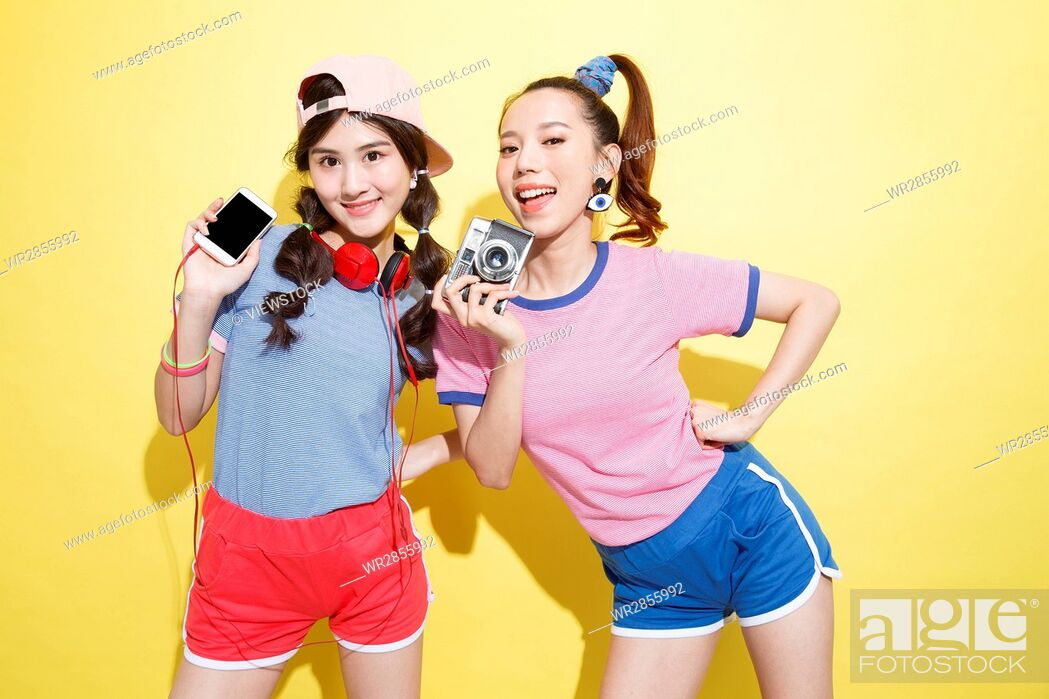 Stock Photo: Happy fashion sisters take the camera to take pictures.