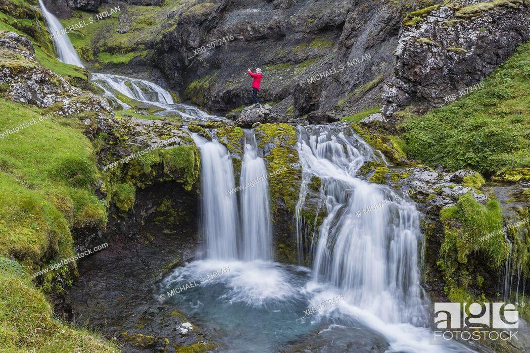 Stock Photo: Photographer at small waterfall just outside the town of Grundarfjörður on the Snæfellsnes Peninsula, Iceland.