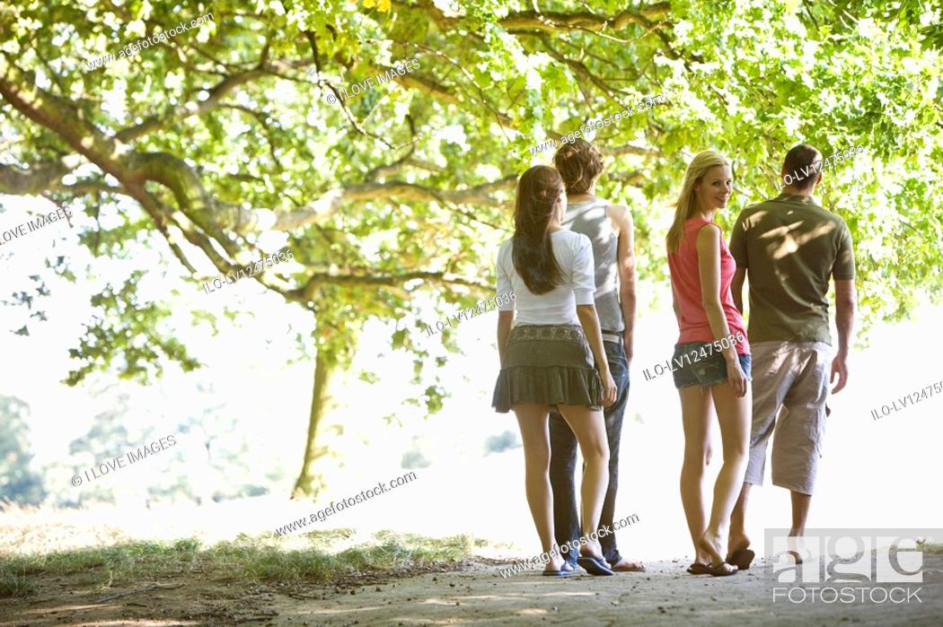Stock Photo: Four friends walking along a path in summertime.
