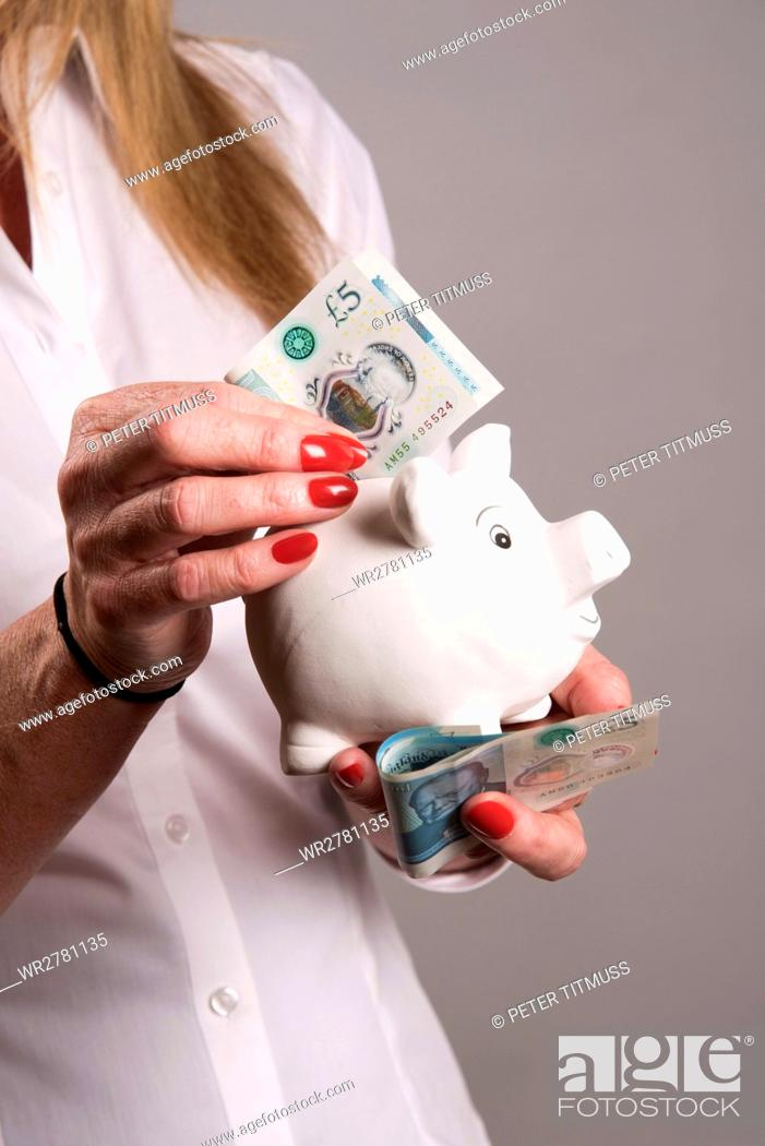 Stock Photo: Woman holding a piggy bank and new five pound notes.