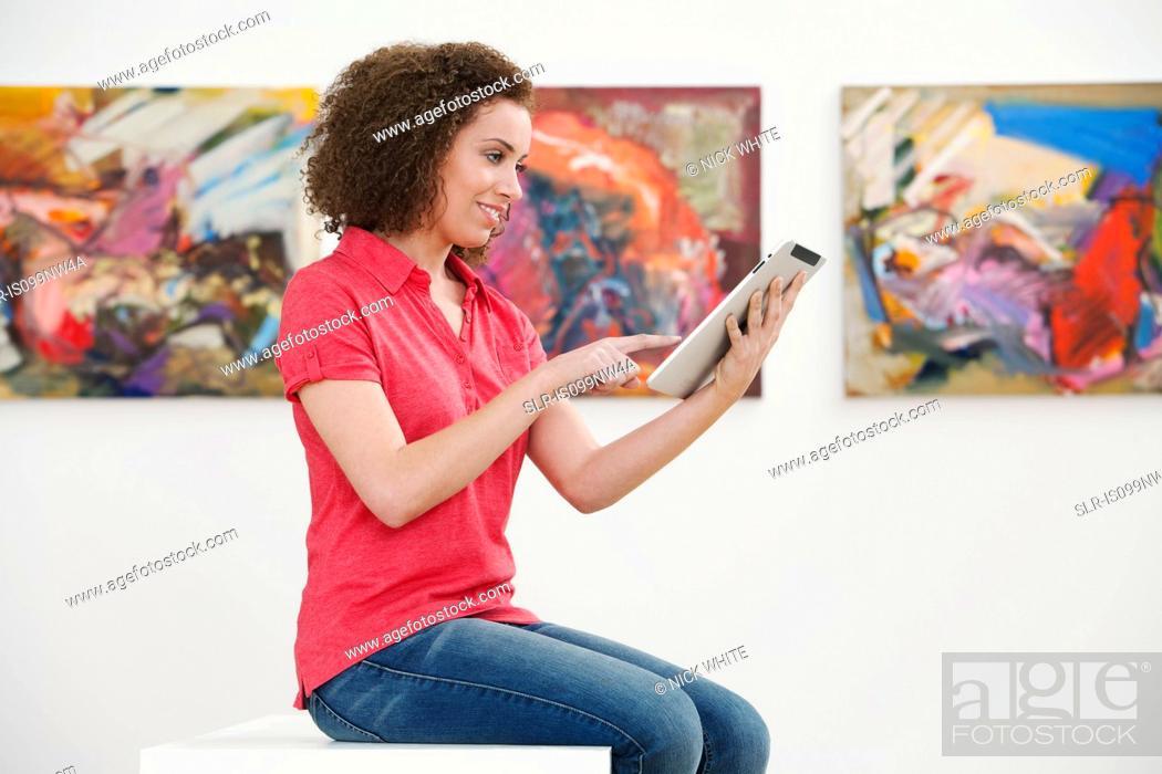 Imagen: Young woman using digital tablet in art gallery.