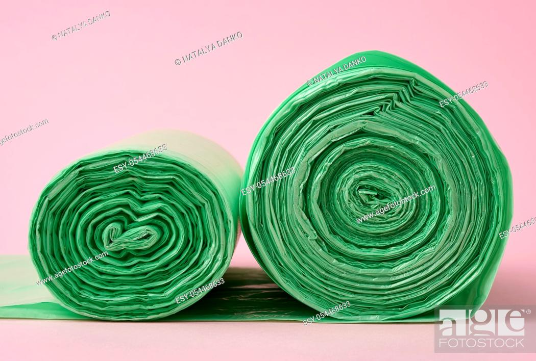Stock Photo: two rolls green plastic bags for trash bin on pink background, close up.