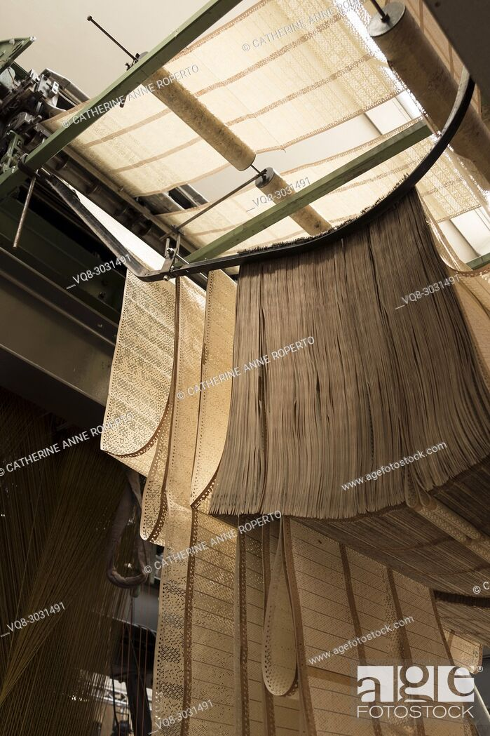 Imagen: Concertina of perforated pattern sheets loop down and over jacquard fabric loom, La Manufacture de Roubaix, France.