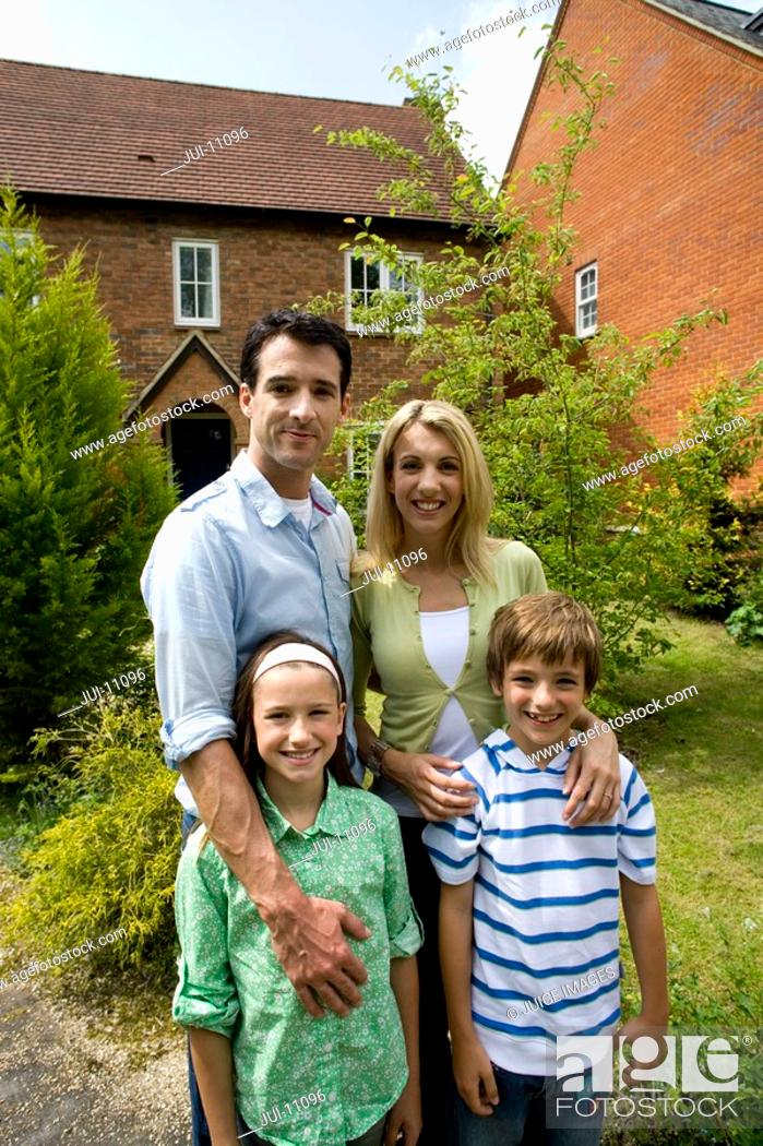 Stock Photo: Family of four outside house, smiling, portrait.