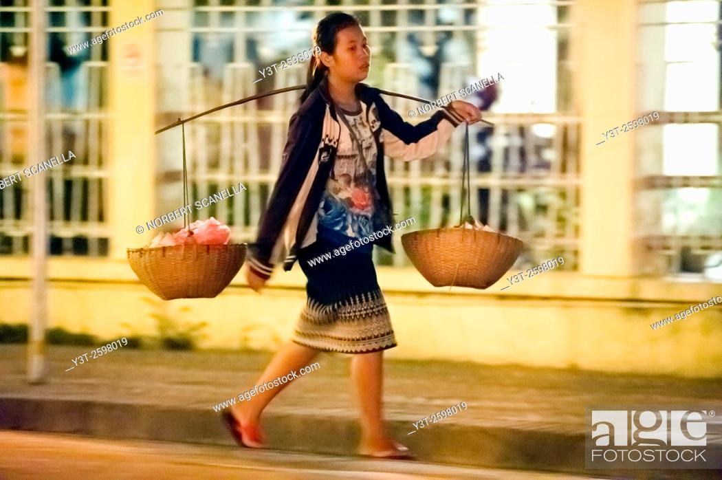Stock Photo: Asia. South-East Asia. Laos. Province of Luang Prabang, city of Luang Prabang, World heritage of UNESCO since 1995. Woman carrying baskets.