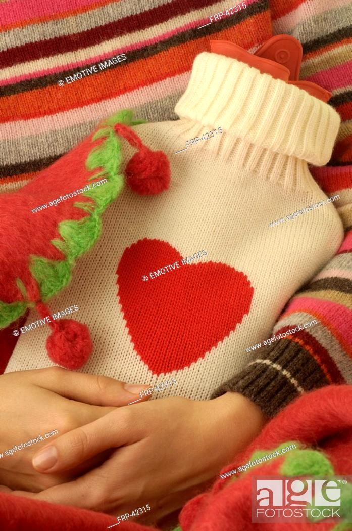 Stock Photo: Hot water bottle in a beige overcoat with red heart.